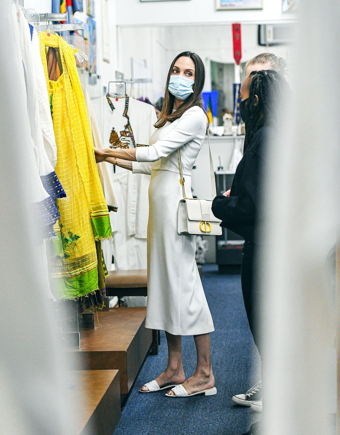 """Angelina Jolie sieht selbst beim Geburtstagsshopping für ihre Tochter Zahara bezaubernd aus. In L.A. wurde die Schauspielerin in diesem basic Luxus-Look gesichtet. Mit eng geschnittenem, weißen Kleid, Fendi-Sandaletten (rund 500 Euro) und der weißen""""30 Montaigne""""-Taschevon Dior (etwa 3000 Euro) stöbert sie gemeinsam mit ihren Töchtern Zahara und Siloh. Die Dior Bag scheint eine ihrer absoluten Lieblinge zu sein, denn die trägt sie bereits seit dem letzten Sommer rauf und runter. Was sollen wir sagen? Können wir total verstehen!"""