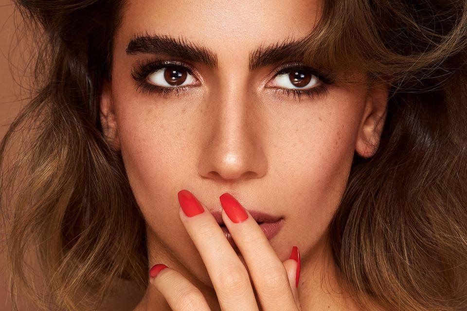 Geschminkte Frau mit lackierten Nägeln hält sich Finger an den Mund