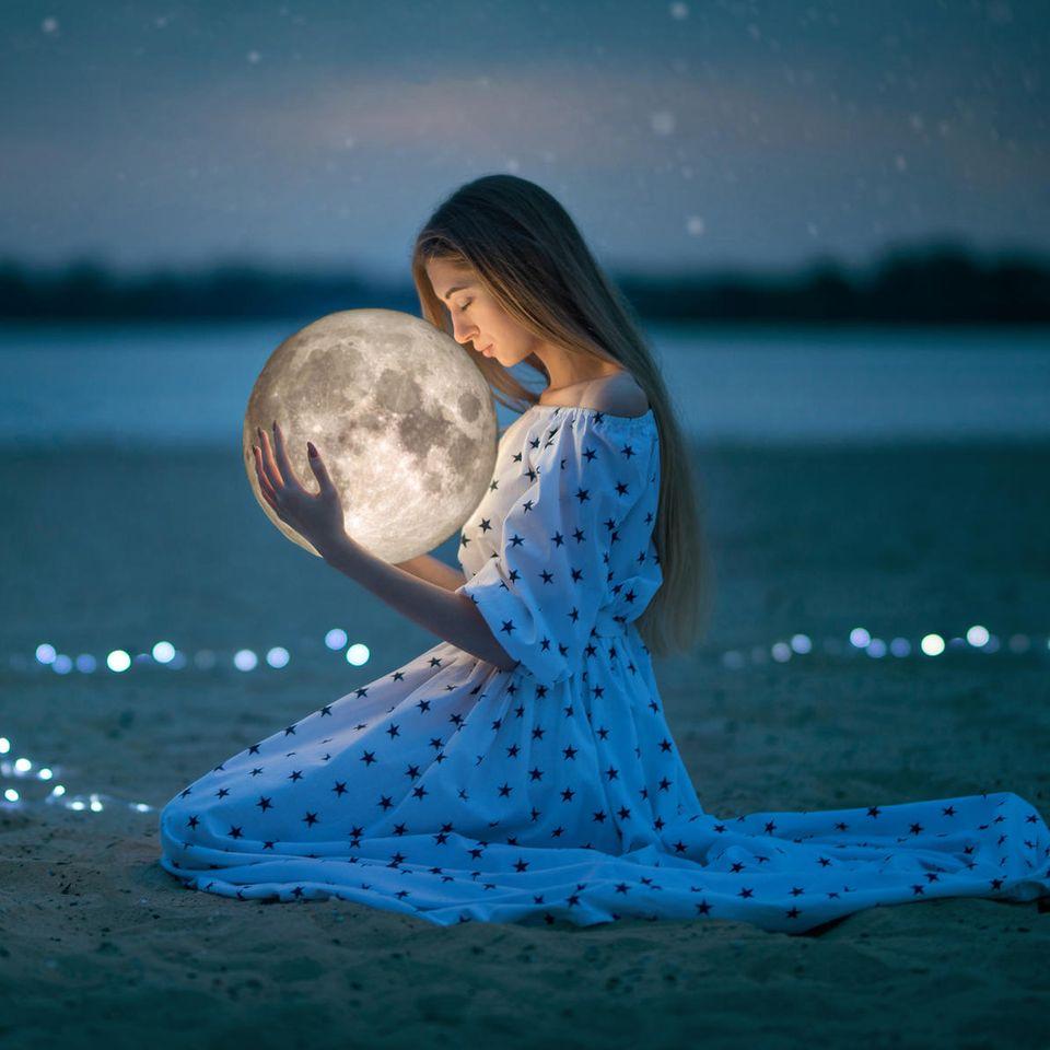 Frau hält einen Mond in der Hand