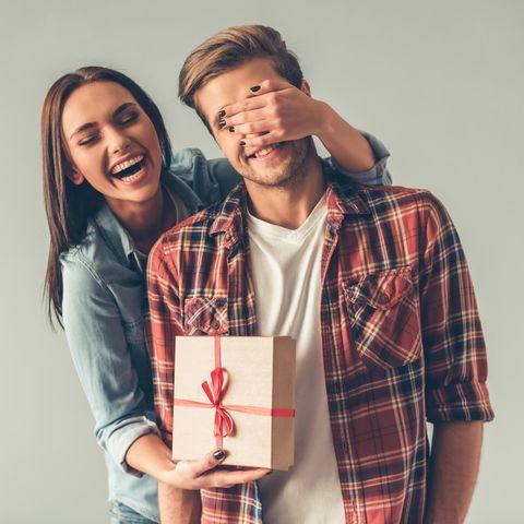 Junge Frau und junger Mann, junge Frau mit Geschenk, Geschenk für den Mann, Geschenk