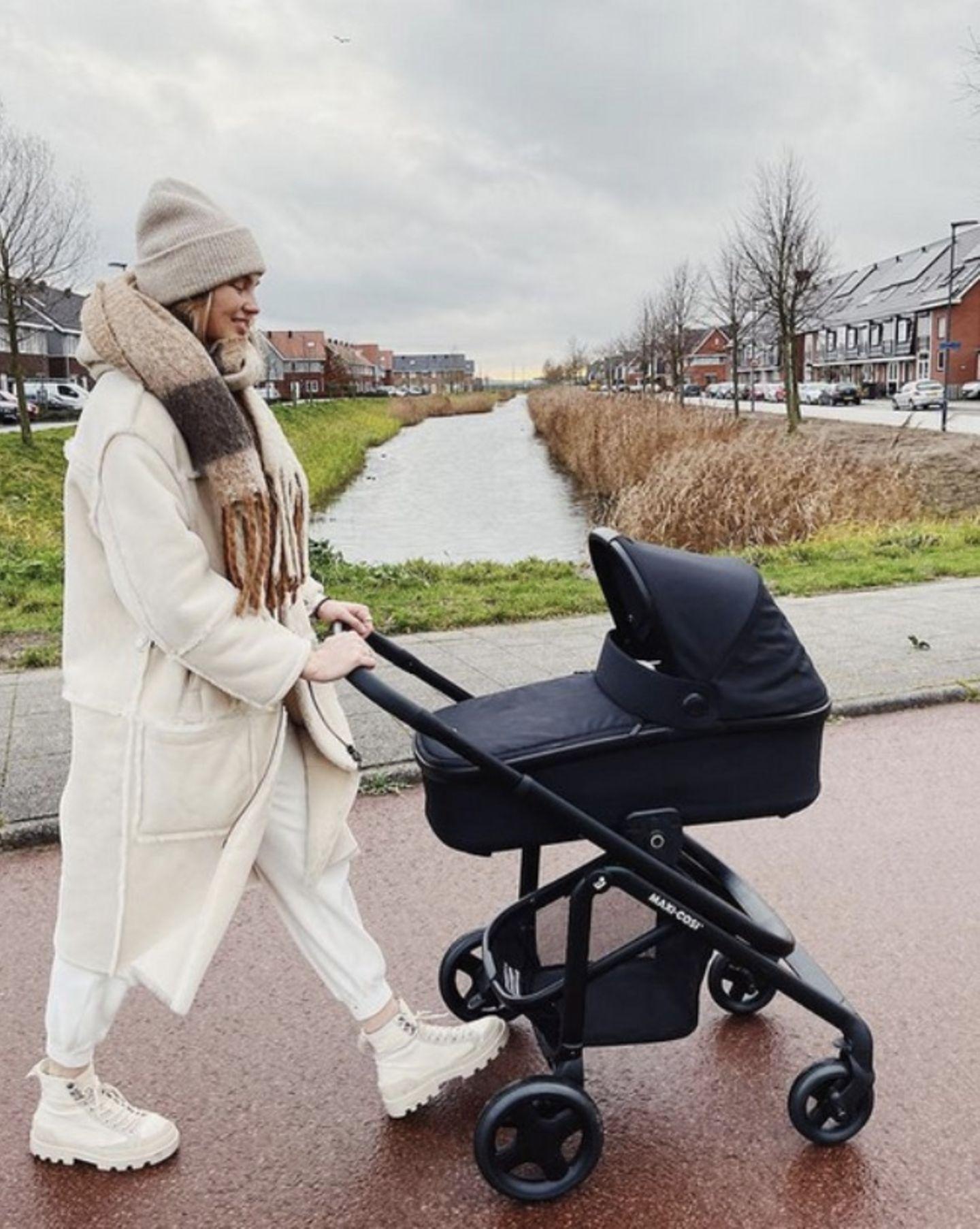 """Voller Stolz fährt """"Victoria's Secret""""-Model Romee Strijd ihre Tochter Mint durch ihre Heimatstadt in Holland. Und natürlich ist nicht nur Romees All-White-Look, sondern auch ihr edler Kinderwagen von Maxicosi ein echter Hingucker. Die hübsche Blondine weiß einfach, was angesagt ist."""