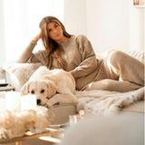 Fashion-Bloggerin Farina Opoku hat es sich mit Hund Oreo auf der Couch bequem gemacht. Wir wissen nicht, was am kuscheligsten aussieht; der Hund, die Decke oder ihr beigerZweiteiler aus Wolle.