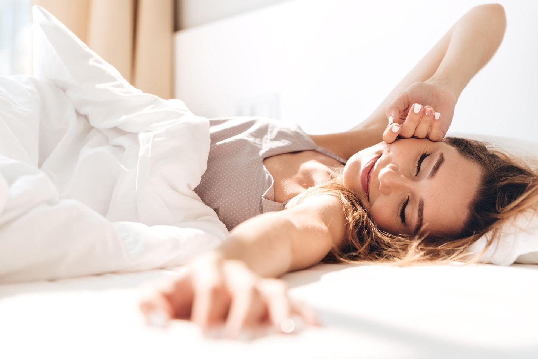 Frau liegt lächeln im Bett und streckt sich