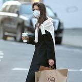 """In New York City ist Katie Holmes auf Shoppingtour. Bei """"Bloomingdales"""" wird die Schauspielerin fündig. Zur Stärkung gibt es anschließend einen Coffee-to-go von """"Starbucks"""". Katie trägt einen dunklen Mantel, einen weißen Schal, Jeans und Slipper."""