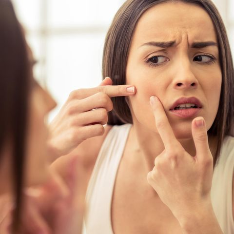 Brünette Frau versucht Unreinheit im Gesichts auszudrücken