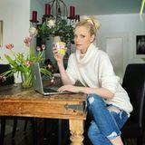 Franziska Knuppe grüßt mit Heißgetränk vor dem Laptop sitzend aus dem Home Office.
