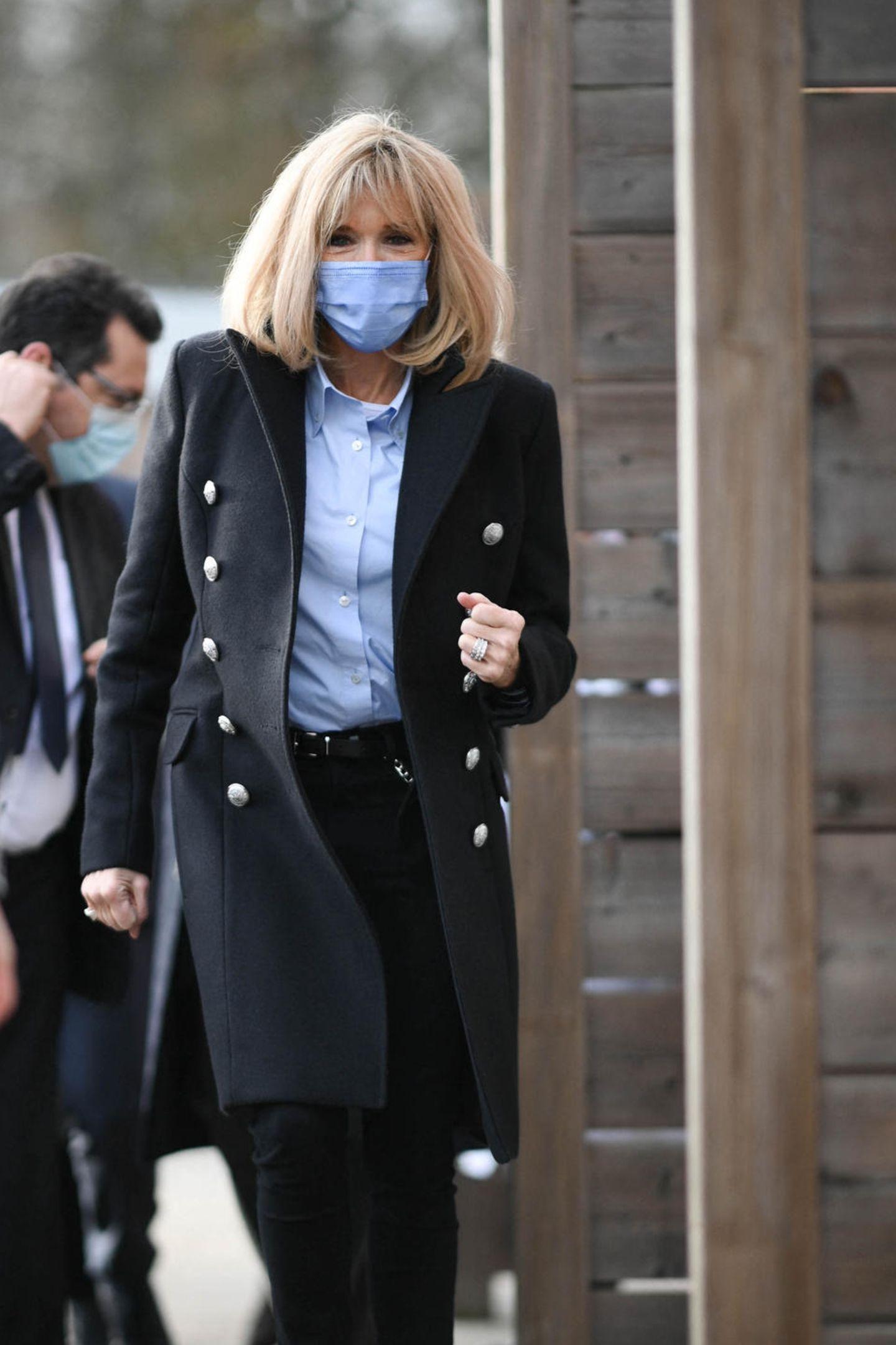 Hier ist mal wieder der Beweis: Brigitte Macron hat einfach Stil! Bei dem Besuch desKinderkrankenhauses in Bullion beweist die französische Première Dame ihr Know How. Sie kombiniert eine klassische Bluse zur engen, schwarzen Jeans. Die Ankle Boots mit derbem Blockabsatz machen das elegante Outfit ein bisschen lässiger – genauso, wie die silberne Kette, die sie seitlich an der Hose trägt. So ein Accessoire haben wir an ihr ja noch nie gesehen, wie ungewöhnlich! Der Wollmantel mit silbernen Knöpfen sorgt wiederumfür die nötige Portion Klasse.
