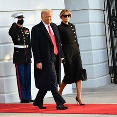 """Ein historischer Moment: Donald Trump und Melania Trump verlassen das Weiße Haus. Für ihren letzten Auftritt als First Lady setzt Melania auf einkomplett schwarzesOutfitbestehend aus einer Chanel-Jacke mit seitlicher Knopfleiste und schienbeinlangem Kleid. Eine elegante Hochsteckfrisur rundet den """"Trauer""""-Look ab."""