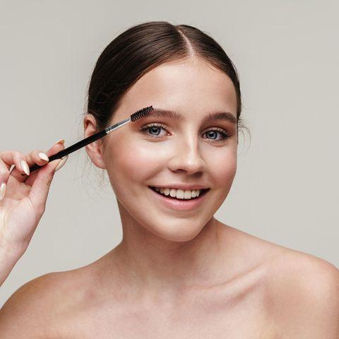 Junge Frau stylt fröhliche ihre Augenbrauen