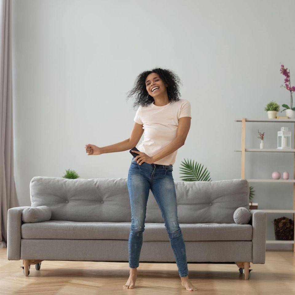 Frau tanzt im Wohnzimmer
