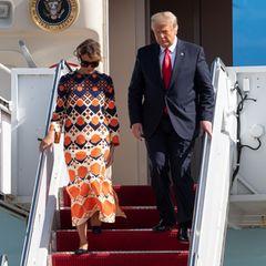 """Das ging ja fix: Während Melania Trump mit ihrem Gatten Donald das Weiße Haus noch im dramatischen, schwarzen Chanel-Look verlässt, zieht sie sich auf dem Flug nach Mar-a-Lago, Florida, schnell um und nutztdie Air Force 1 wie die glitzernde Umziehkugel der """"Mini Playback Show"""". Heraus kommt Melania dann im bunten Hippie-Look von Gucci. Na dann, bye bye und viel Spaß beim Golf-Zuschauen in Florida!"""