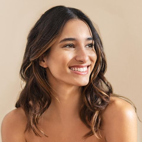 Schöne Frau mit offenen Haaren lächelt in die Ferne