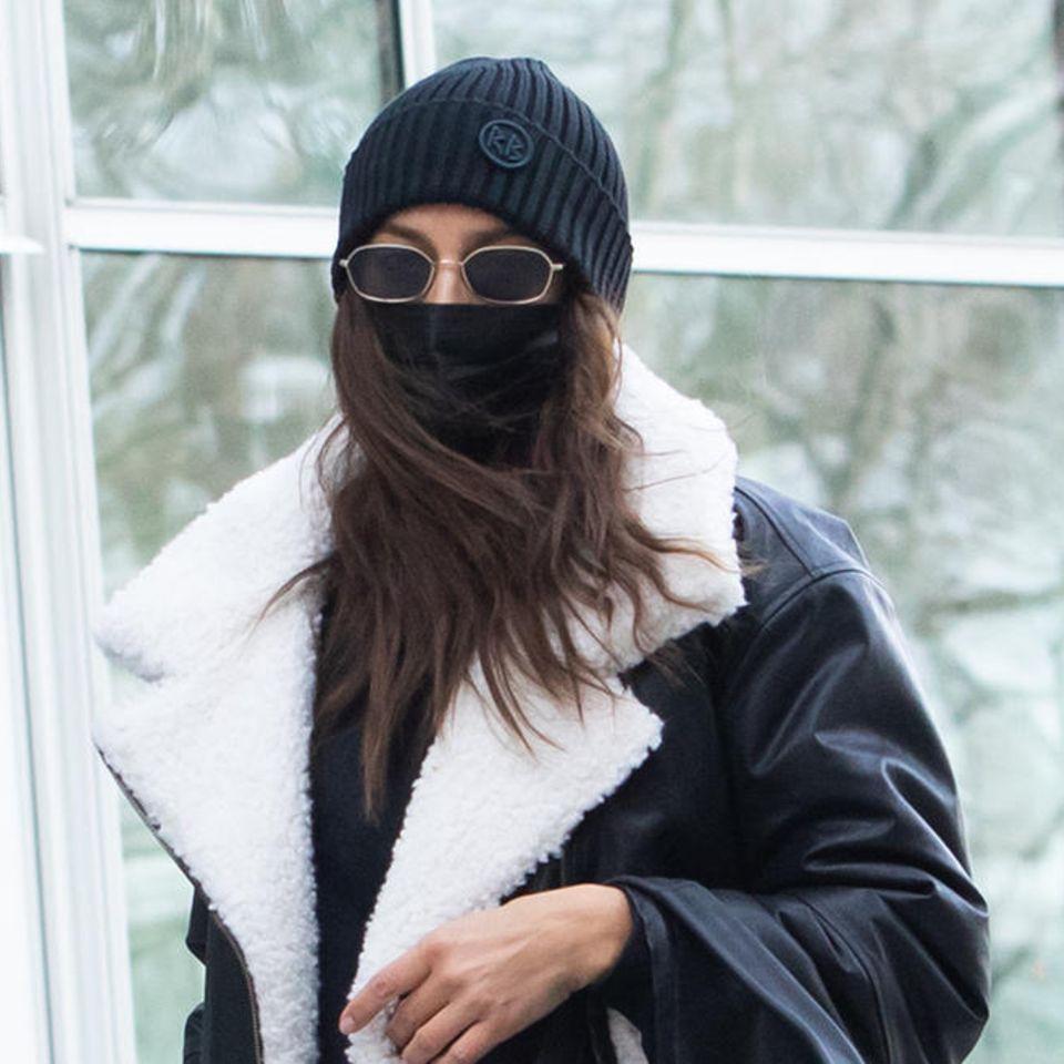 Irina Shayk ist de Königin der Lässig-Looks. Kaum ein Tag vergeht, an dem das Supermodel nicht in einem aufregenden Look auf den Straßen New Yorks unterwegs ist. Ihr neuester Fashion-Coup: eine Retro-Jogginghose zum Knöpfen von Addidas und eine gefütterte Pilotenjacke. Ein Look, der wohl bei denwenigsten so cool aussehen würde. Dazu Strickmütze, Sonnenbrille und Mund-Nasen-Schutz – und schon sind Irina Shayk und Töchterchen Lea de Seine, die sie vor sich im Kinderwagen schiebt, beinahe inkognito unterwegs.