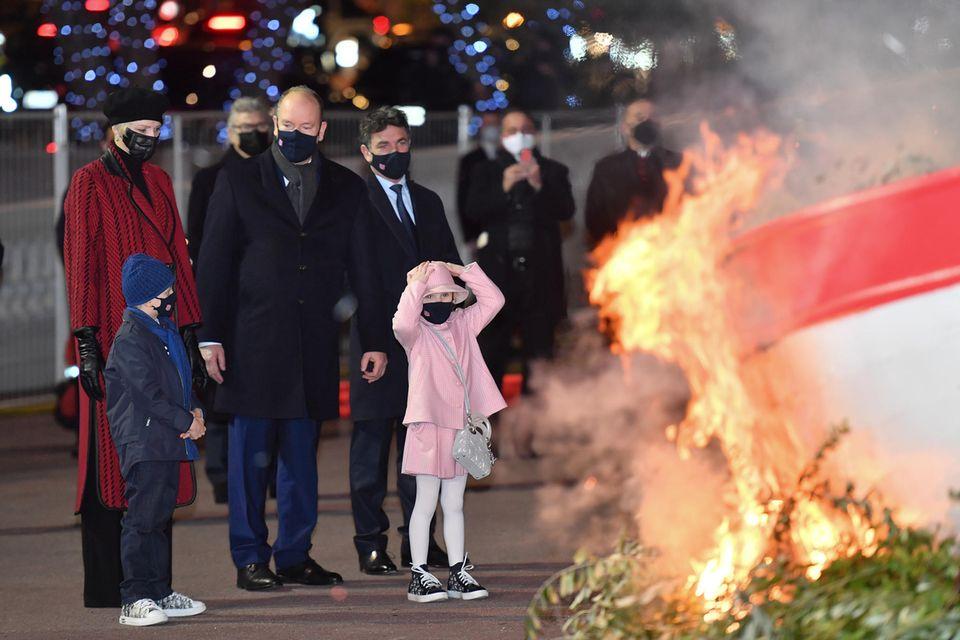 Dabei jagen die aufsteigenden Flammen der kleinen Gabriella einen ordentlichen Schrecken ein, aber für den Mndestabstand zum Feuer haben Fürst Albert und Fürstin Charlène schon gesorgt.