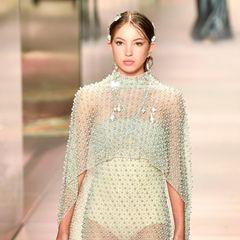 Zart wie eine Elfe schwebt Lila Moss über den Catwalk. Sie trägt ein leicht durchsichtiges mit Perlen besticktes Kleid.