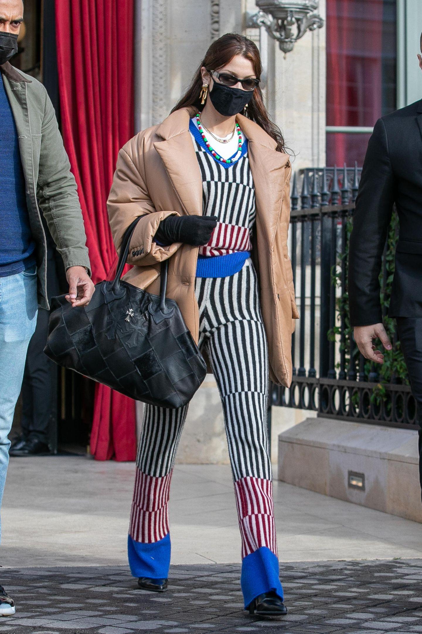 Tja, trotz Längsstreifen ist dieser Look von Bella Hadid alles andere als vorteilhaft: Pyjama-Ensemble, dazu Daunenjacke und 90s-Accessoires – hier passt nix zusammen.