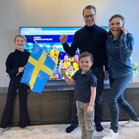 Prinz Frederik telefoniert mit Prinzessin Victoria, die mit Prinzessin Estelle, Prinz Oscar und Ehemann Prinz Daniel im Wohnzimmer steht.