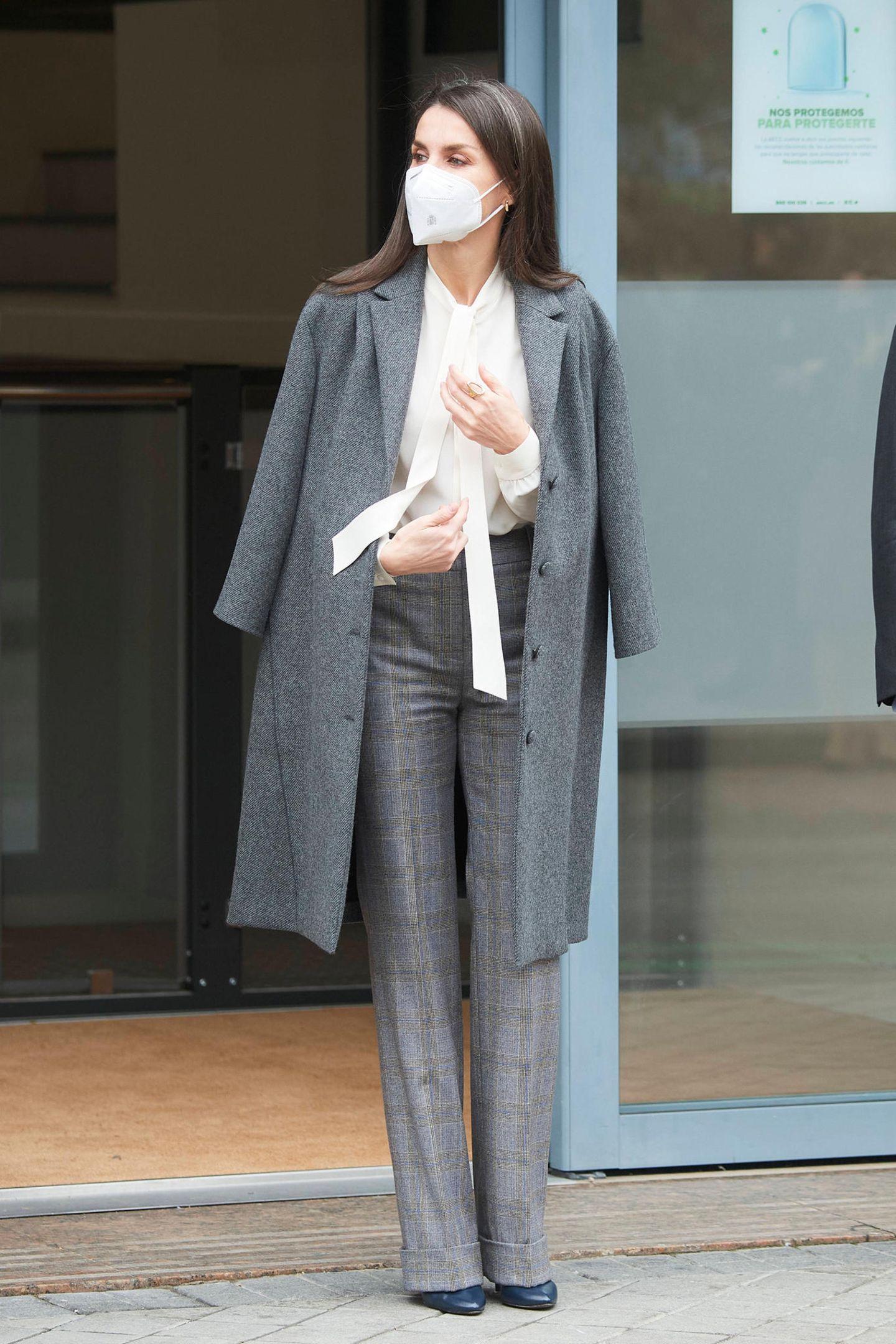 Bei diesem wichtigen Termin zum Kampf gegen Krebserkrankungenzeigtsich auch Königin Letizia beim Style zurückhaltend. Sie trägt eine weiße Schluppenbluse von Hugo Boss, einen grauen Mantel von Nina Ricci und eine Anzughose von Massimo Dutti. Eine Sache an ihr fällt aber auf ...