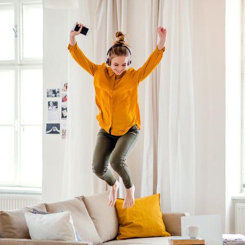 Frau springt auf dem Sofa