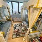 """Ein kuscheliger Teppich mit Tiermotiven bildet den Mittelpunkt des Raumes, der an beiden Seiten mit Stoff verzierte """"Häuschen"""" zum Schlafen oder Spielen bietet."""