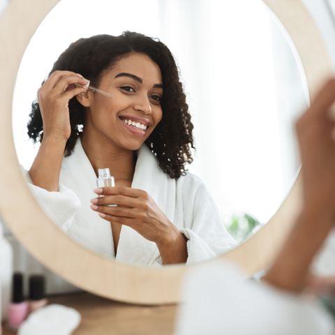 Schöne Frau benutzt Gesichtsöl vor dem Spiegel