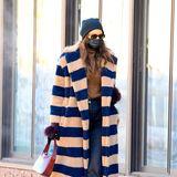 Irina Shayk ist trotz gedeckter Farben in ihrem Blockstreifen-Mantel (ca. 2500 Euro) von Max Maranicht zu übersehen. Dazu trägt sie Schutz-Boots, einen Kaschmirpullover von Falconeri, Tasche von By Farund Sonnenbrille und Hose des Labels Chrome Hearts.