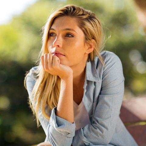 Hochstapler-Syndrom: Blonde Frau stützt den Kopf mit der Hand ab und denkt nach.