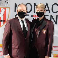 """Sowohl Fürst Albert als auch FürstinCharlène tragen bei dem Event einen violettfarbenenBlazer mit besticktem Wappen darauf. Hierbei handelt es sich um das Logo der """"FédérationMonégasquede Rugby"""". Mit dem recht steifen Businesslook zeigt das Fürstenpaar ihre Unterstützung derRugbymannschaften von Monaco."""