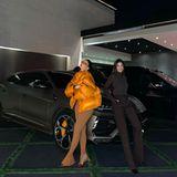 Kylie und Kendall lehnen lässig an einem Lamborghini Urus. Die orangefarbene Daunenjacke der jüngsten Schwester des Kardashian-Jenner-Clans ist perfekt auf den orangefarbenen Bremssattel abgestimmt.