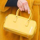 Zum gelben Mantel kombiniert sie eine farblich passende Mini-Bag, die aktuell voll im Trend liegen. Die Tasche ist nicht nur wegen Form und Farbe ein Highlight, mit einemPreis von ca. 126 Euro können wir sie uns auch leisten.