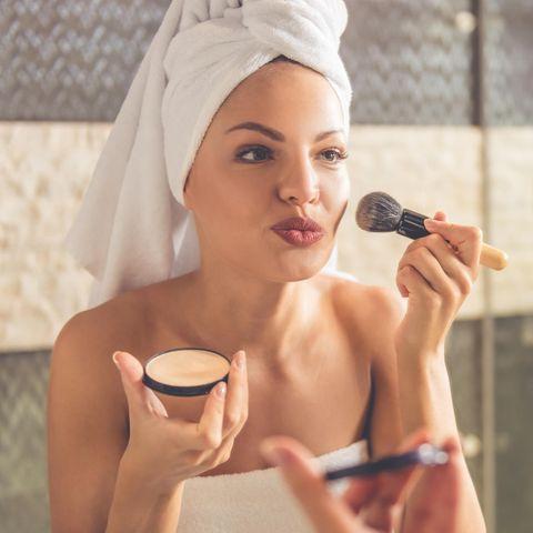 Schöne Frau schminkt sich mit Puder im Badezimmer