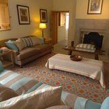 """Landhaus-Möbel, warme Farbenund ein Kamin sind im """"Sitting Room"""" von besonderer Bedeutung. Hier nehmen gerne und oft Gäste auf den tiefen Sofas mit farblich abgestimmten Kissenbezügen Platz."""