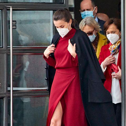Einen ganz ähnlichen Look trug nämlich Königin Letiziabeim Besuch einer Ausstellungin der Nationalbibliothek in Madrid am 16. Februar. Sie setzte ebenfalls auf das erschwingliche Kleid von Massimo Dutti. Sie kombinierte es allerdings mit einem schwarzen Mantel und roten Pumps.
