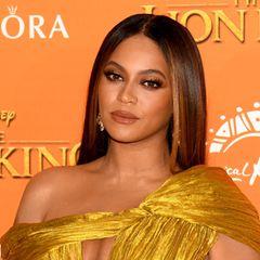 """In Gold gehüllt präsentiert sich Beyoncé bei der """"König der Löwen"""" Premiere. Auch ihr Augen-Make-up hält sie in Gold und Braun-Tönen. Um die Partie optisch zu vergrößern, blendet sie den Lidschatten auch großzügig am unteren Wimpernkranz aus. Falsche Wimpern geben dem Look den Glamour-Faktor."""