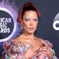 """Sängerin Halsey liebt extravagante Looks. Das stellt sie auch bei den American Music Awards unter Beweis. Ihre Augenbrauen deckt sie dafür vollständig ab, sodass der künstlerisch bunte Lidschatten noch mehr zur Geltung kommt. Ihr Make-up macht sie immer selbst – 2021 launchte sie ihre Beauty-Marke """"About Face""""."""
