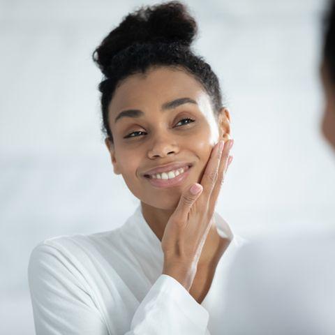 Schöne Frau im Bademantel steht vor dem Spiegel und benutzt Gesichtscreme