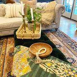 Mit viel Liebe zum Detail haben Tori Spelling und ihreInterior Designerin Holzschalen, Messing-Kerzenständer und ein Bambustablett als Eyecatcher auf der Samtbank dekoriert.