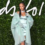 """2019  Während es musikalisch eher ruhig um Rihanna geworden ist, hat sie sich mit ihrem Label """"Fenty"""" einen Namen in der Mode-Branche gemacht. Bei den """"British Fashion Awards"""" zeigt sie sich in einem engen glänzenden Kleid zu dem sie einen auffälligen Choker und einen Tüll-Mantel kombiniert."""