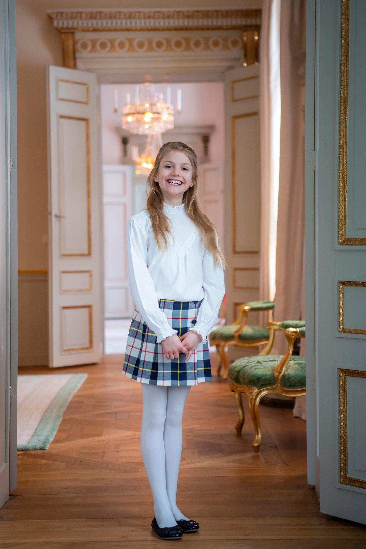 Estelle ist einfach ein absoluter Sonnenschein!In edler Bluse, kariertem Minirock und weißer Strumpfhose posiert sie stolz im Schloss.