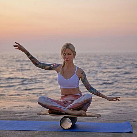 Balance Board: Die besten Bretter und Tipps, junge Frau, Yoga, Pose