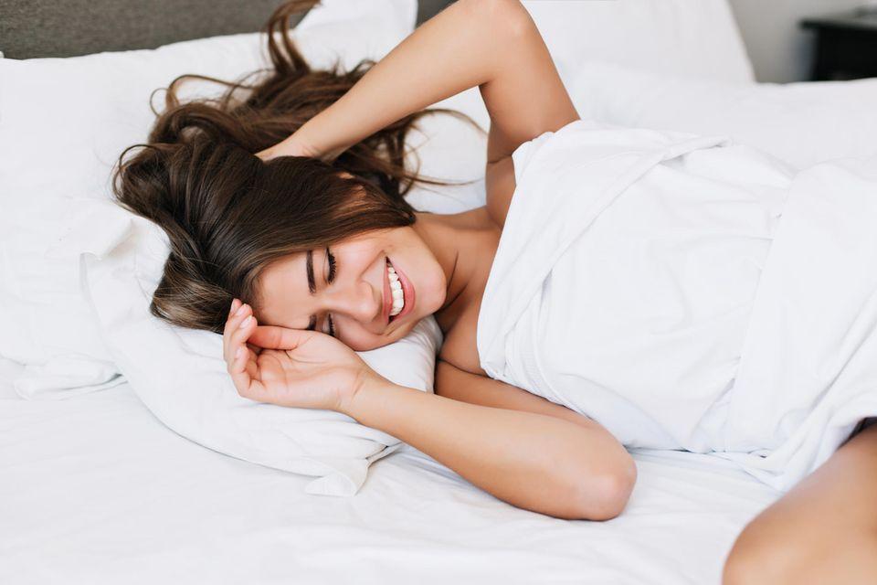 Frau im Bett, glückliche Frau unter einer Bettdecke