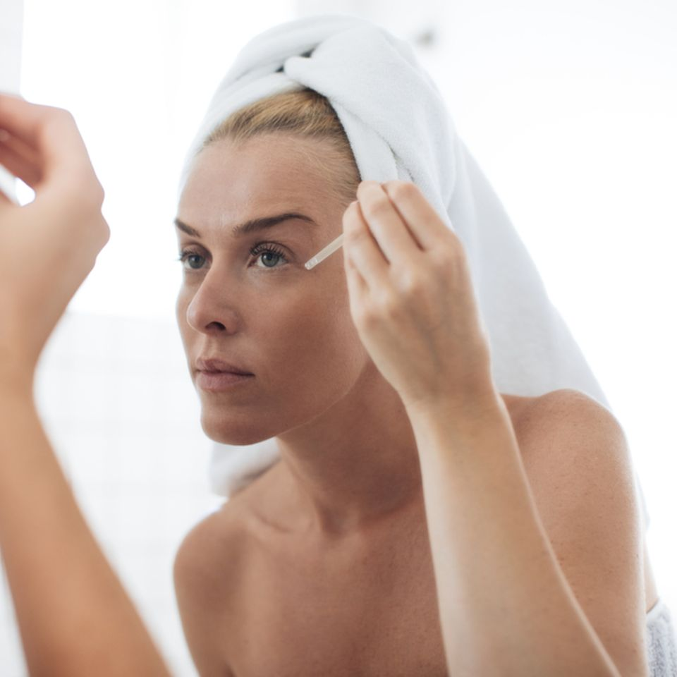 Schöne Frau mit weißem Handtuch auf Kopf benutzt Gesichtsserum vor dem Spiegel im Badezimmer.