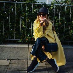 Die ersten frühlingshaften Tage sind da und Moderatorin Victoria Swarovski greift passend dazu zum sonnengelben Mantel. Warum der Look nicht zu sommerlich wirkt? Die 27-Jährige wählt nicht nur dunkle Töne für ihren restlichen Look sondern setzt auch auf eine Leder-Culotte. Sneaker in Schwarz, ihre ebenfalls schwarze Chanel-Bag sowie Sonnenbrille und Cap runden den Look perfekt ab.