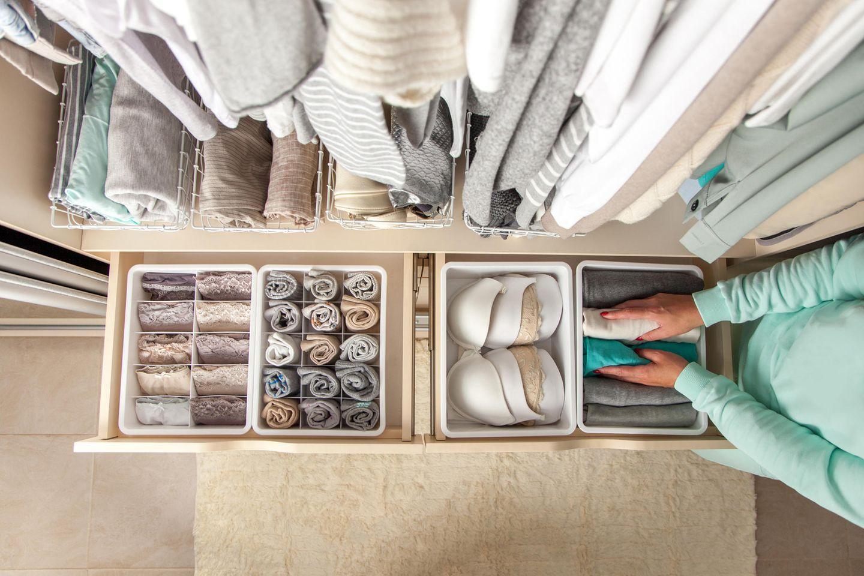 Ordnung schaffen, aufgeräumter Kleiderschrank, Frau räumt Kleiderschrank auf