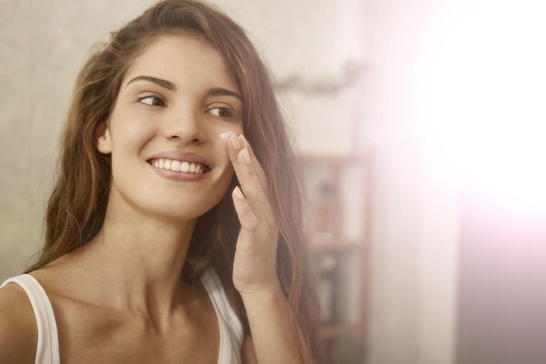 Schöne Frau mit braunen Haaren trägt Creme vor dem Spiegel auf ihr Gesicht auf.
