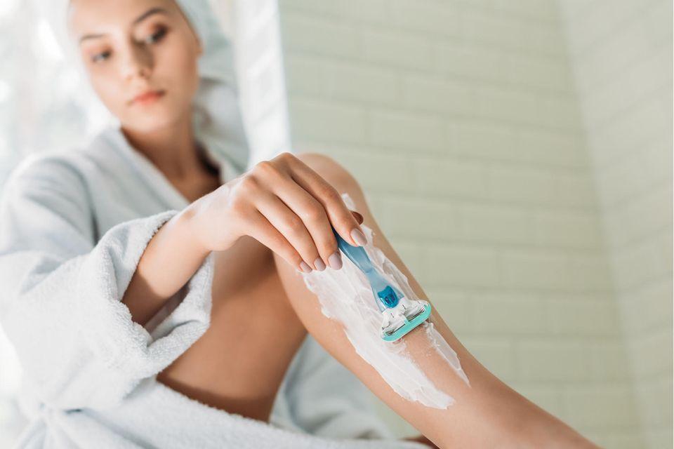 Damenrasierer-Test: Die besten Modelle für eine angenehme Rasur, Junge Frau rasiert sich die Beine