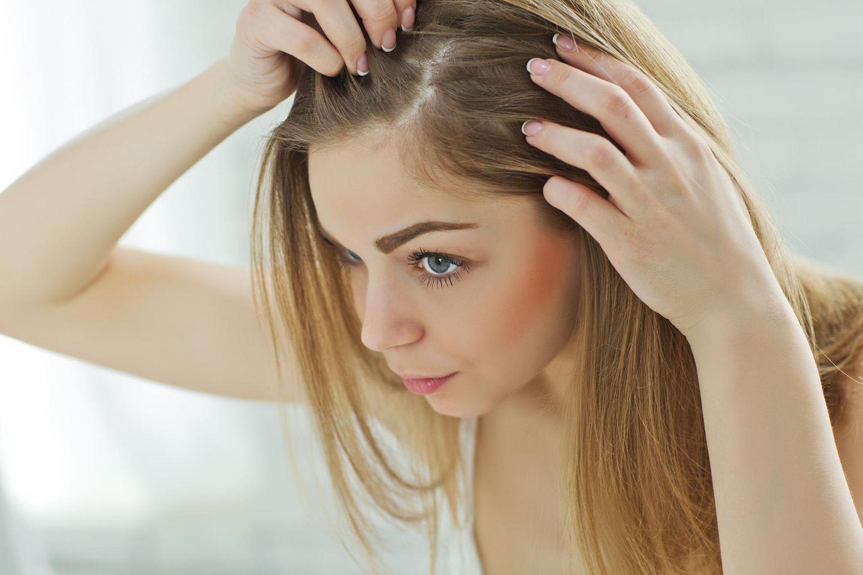 Ihre Haarfarbe hält nich? Frau zeigt ihren Haaransatz