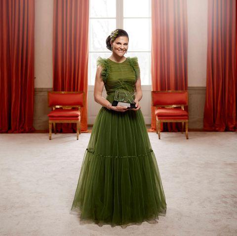 """Wow! Victoria von Schweden sieht auf diesem Foto fast aus, wie eine Disneyprinzessin. Die Kronprinzessin posiert anlässlich ihrer """"Hetero of the Year""""-Auszeichnung vor roten Vorhängen unter einem riesigen Kronleuchter. In ihrem dramatischen Tüllkleid von H&M Concious und mit aufwendigem Kopfschmuck von Maria Nilsdotter sieht sie einfach nur umwerfend aus."""