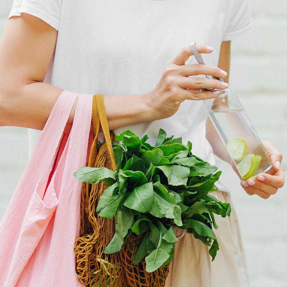 Nachhaltig einkaufen, Frau mit Leinentasche, Gemüsenetz und Trinkflasche