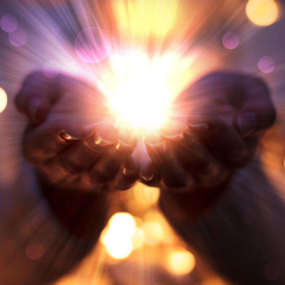 Aura Farben: Frauenhände, aus denen ein Leuchten hervorgeht.